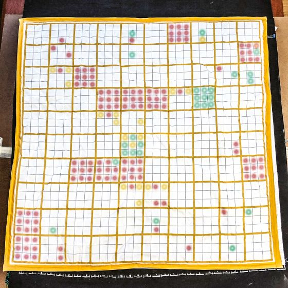 A photograph of a tactile, interactive quilt version of Peabody's chart of significant events from the 17th century. The quilt has a white background with a yellow border. Within it, the thick yellow lines create a 10 x 10 grid. The smaller subdivisions of 9 squares within each square, which represent the type of significant event, is created by thinner gray lines. The squares aren't completely shaded, as in Peabody's original chart, but rather are occupied by colored circles.