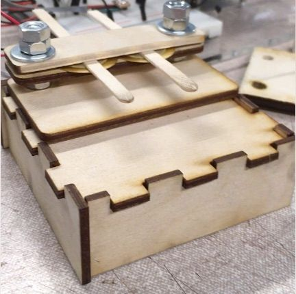 Two coffee stirrers are clamped between small pieces of wood with brass piezo discs fixed in place underneath each stirrer. The assembly sits on a larger wooden box.