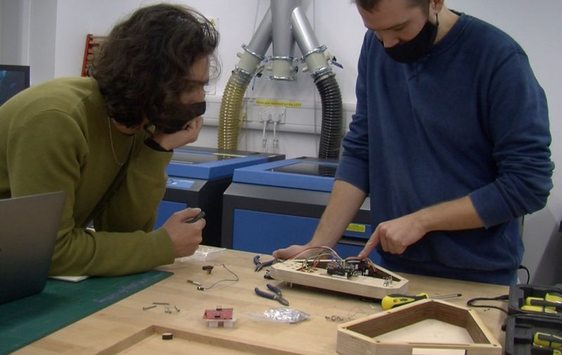 Two people in facemasks look closely at a disassembled instrument comprised of a wooden structure and electronic components.