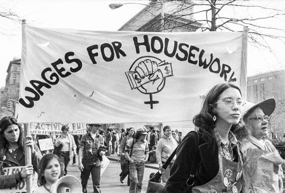 """A black and white photograph of activists, mostly women, at a Wages for Housework march in 1977. The activists fill the streets, with two near the front holding up a poster which reads """"WAGES FOR HOUSEWORK"""" and has a drawing of the women's gender symbol, modified to display a fist grasping cash instead of the standard circle."""