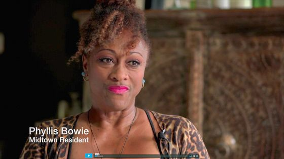 """A screenshot of a video from the Narratives of Displacement and Resistance, showing Phyllis Bowie, a middle-aged Black woman with hot-pink lipstick and brown hair in a bun. In the bottom left corner of the frame, a caption reads """"Phyllis Bowie, Midtown Resident."""""""