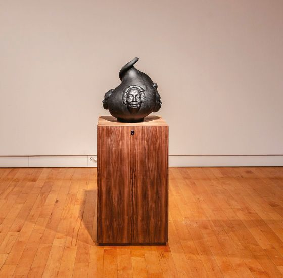A black, dumpling-shaped artifact sits on a rectangular wooden display in a museum. There are faces extruding out from the sides of the object, representing members of a multigenerational Black American family. The artifact is voice-interactive and has an opening at the top, which individuals can speak into and get a response from.