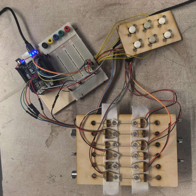 A square piece of wood has six short lengths of guitar string attached. Each string is terminated at either end by separate bridge pieces. Several wires connect the first piece with a smaller piece of wood with six buttons embedded. Both of these pieces are also connected via several wires to a breadboard with a Bela microcontroller connected