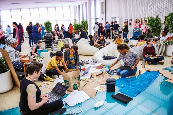 The image shows a group consisting primarily of women, representing many different ages and races, all seated in an open gathering area at the 2018 Make the Breast Pump Not Suck Hackathon. A small group of participants sit on the floor directly in front of the camera, working with their laptops out. In the background, there are more people engaging each other in conversation, a few of which have babies with them.