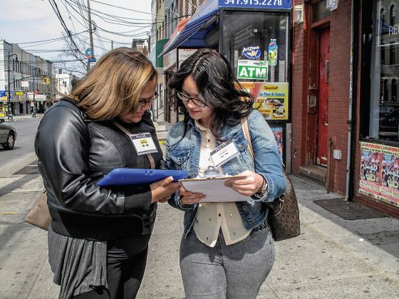 """A photograph of two  high school students standing on a sidewalk in Brooklyn. The student on the left, a young woman who has shoulder-length light-brown hair and is wearing a black leather jacket, is holding a digital tablet while the student on the right, a young woman who has long black hair and is wearing a blue jean jacket over a white shirt, is holding a clipboard. Both students are looking down at the objects in their hands, and both have a badge clipped to their clothing which reads """"PRESS"""" and """"OFFICIAL STUDENT INTERVIEWER."""""""