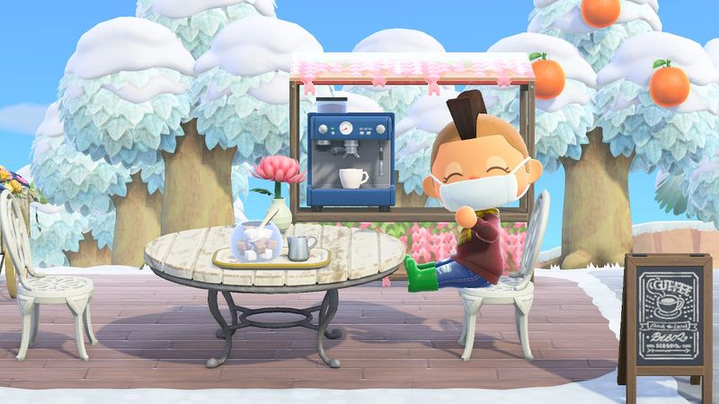 Screenshot from Animal Crossing: New Horizons. The player's avatar sits at an outdoor cafe wearing a disposable 'Doctor's Mask'
