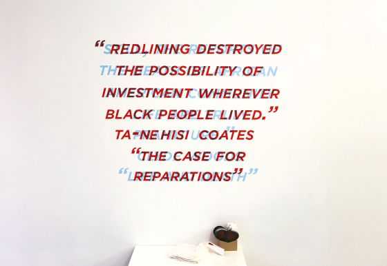 """A photograph from the installation of the artwork Decoding Possibilities by Romi Morrison and Treva Ellison. The image shows two quotes directly overlaid on one another. One quote is in bright blue, while the other is in dark red. The quote in dark red reads """"REDLINING DESTROYED THE POSSIBILITY OF INVESTMENT WHEREVER BLACK PEOPLE LIVED."""" TA-NEHISI COATES """"THE CASE FOR REPARATIONS."""""""" The quote in bright blue is not discernible underneath the darker, red quote. Below the artwork is a pile of 3-D glasses, suggesting that the second quote can be read once the viewer puts on the glasses."""